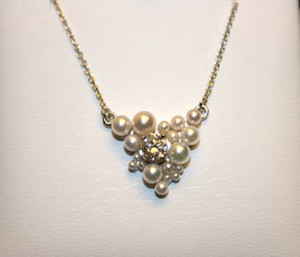 This is quite the impressive piece! One of a kind hand-made necklace with one diamond in the center, offset with different shades of cultured pearls.